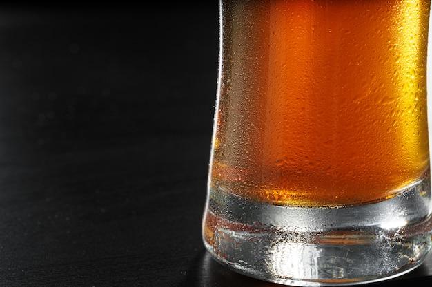 Copo de cerveja em fundo preto, copie o espaço