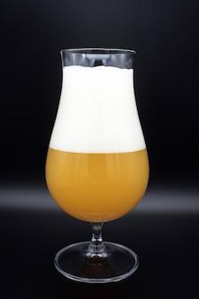 Copo de cerveja em fundo preto, copo de cerveja, recipiente com líquido turvo amarelo