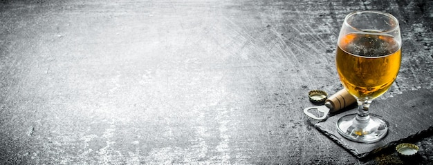 Copo de cerveja em um carrinho de pedra. na mesa rústica preta