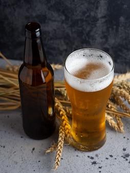 Copo de cerveja em uma pedra escura com garrafa de cerveja e trigo