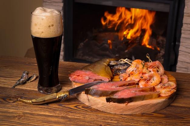 Copo de cerveja escura e uma bandeja com peixes variados no fundo de uma lareira a lenha