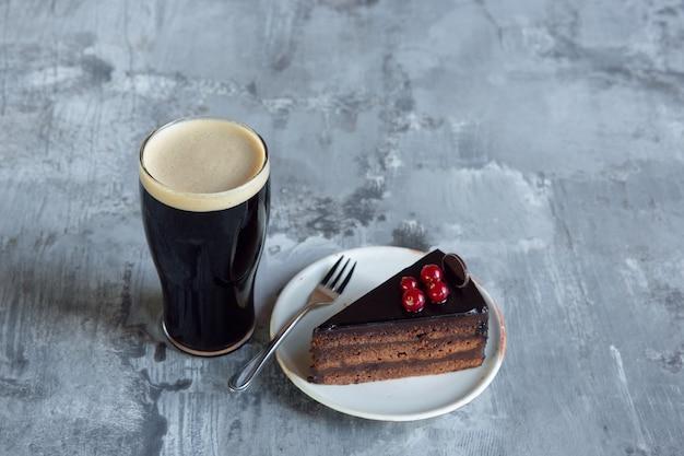 Copo de cerveja escura na mesa de pedra.
