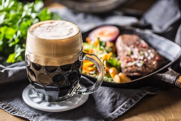 Copo de cerveja escura no bar ou restavurant na mesa com comida delicoius. Foto Premium