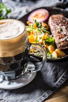 Copo de cerveja escura no bar ou restavurant na mesa com comida delicoius.