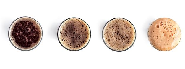 Copo de cerveja escura no fundo branco vista de cima