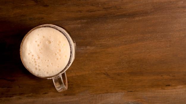 Copo de cerveja espumosa na mesa de madeira
