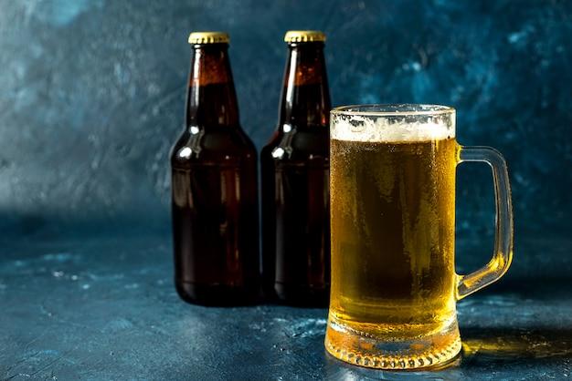 Copo de cerveja gelada e garrafa na mesa de pedra cinza