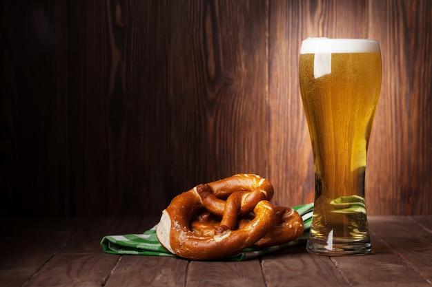 Copo de cerveja lager e pretzel na mesa de madeira. ver com espaço de cópia