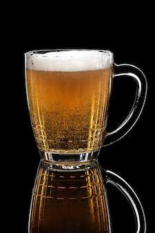 Copo de cerveja lager na mesa preta