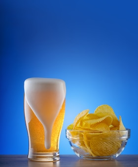 Copo de cerveja light com manchas de espuma e batatas fritas onduladas
