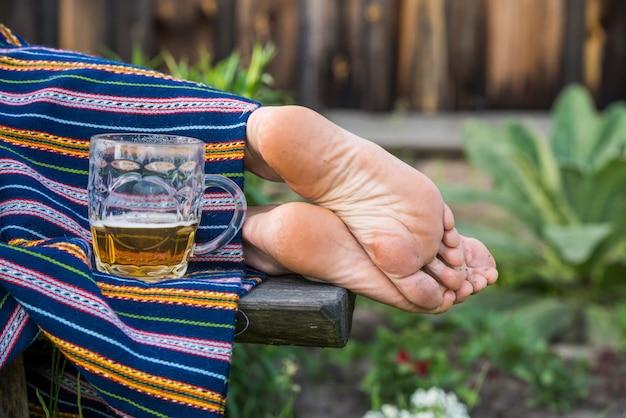 Copo de cerveja light e mulher com os pés descalços, ligo