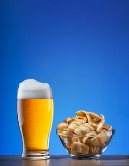 Copo de cerveja light e prato de batatas fritas em azul