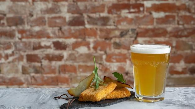 Copo de cerveja light na mesa de pedra e a parede de tijolos.
