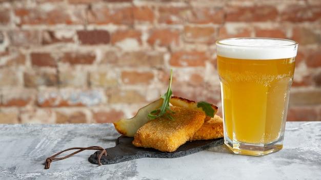 Copo de cerveja light na mesa de pedra e parede de tijolos