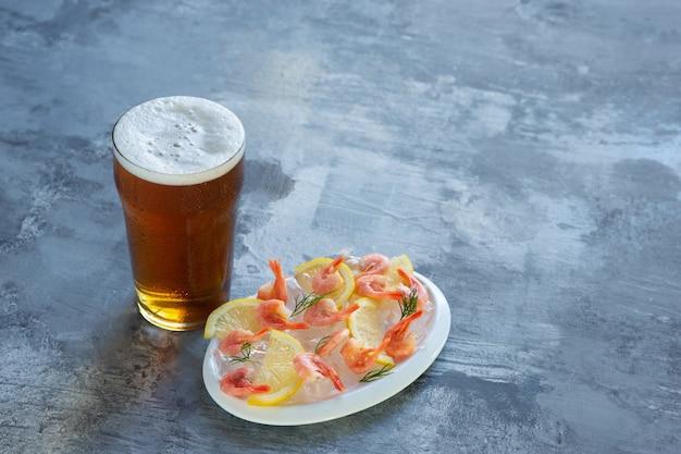 Copo de cerveja light na parede de pedra branca. álcool gelado e camarão com limão são preparados para a festa de um amigo. conceito de bebidas, diversão, comida, comemoração, reunião, oktoberfest.
