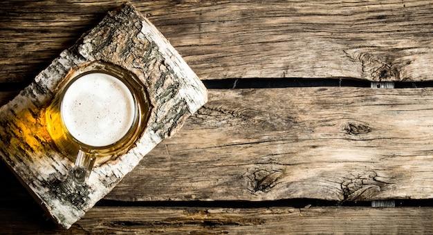 Copo de cerveja light no carrinho de bétula em uma mesa de madeira.