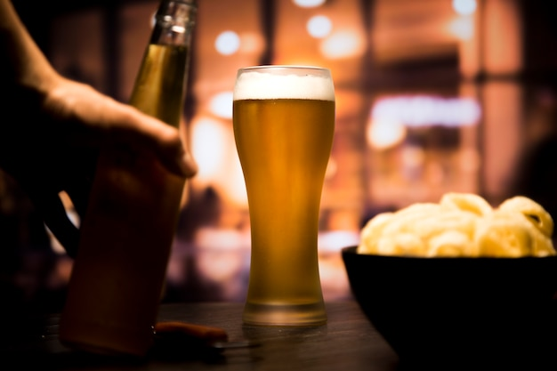 Copo de cerveja na frente do fundo desfocado