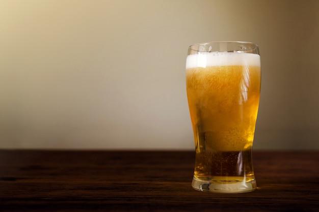 Copo de cerveja na mesa de madeira.
