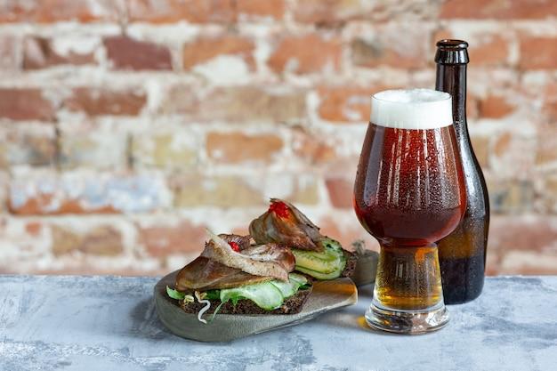 Copo de cerveja na mesa de pedra e a parede de tijolos.