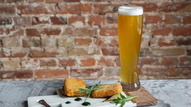 Copo de cerveja na mesa de pedra e parede de tijolos