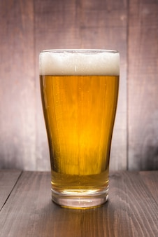 Copo de cerveja no fundo de madeira