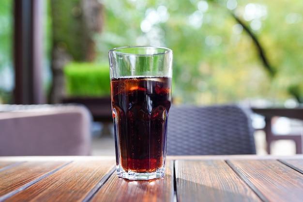 Copo de cerveja preta na mesa de madeira de um restaurante