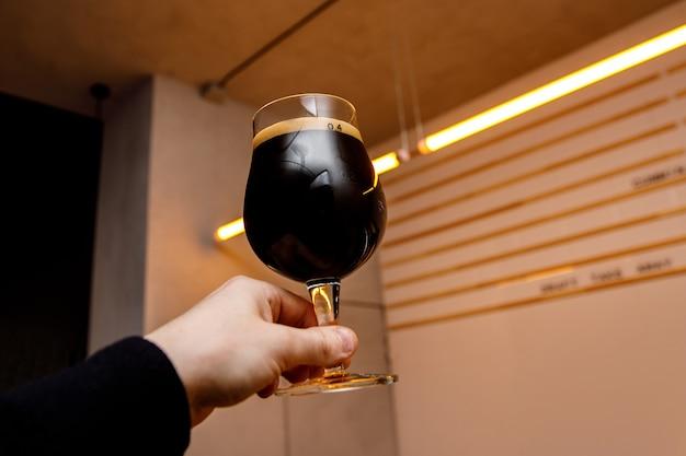 Copo de cerveja preta nas mãos. interior do pub