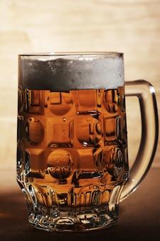 Copo de cerveja sobre a superfície de madeira