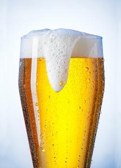 Copo de cerveja transbordando com um pouco de condensação