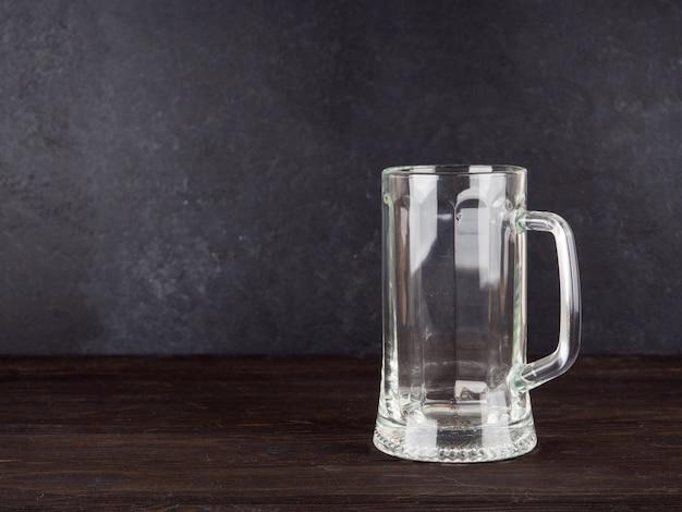 Copo de cerveja transparente vazio no fundo de madeira