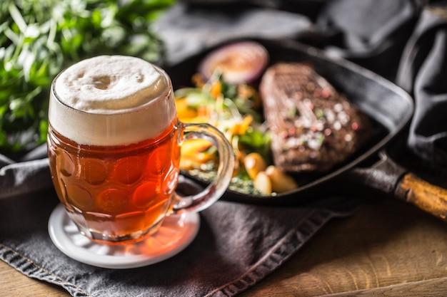Copo de cerveja vermelha no bar ou restavurant na mesa com comida delicoius.