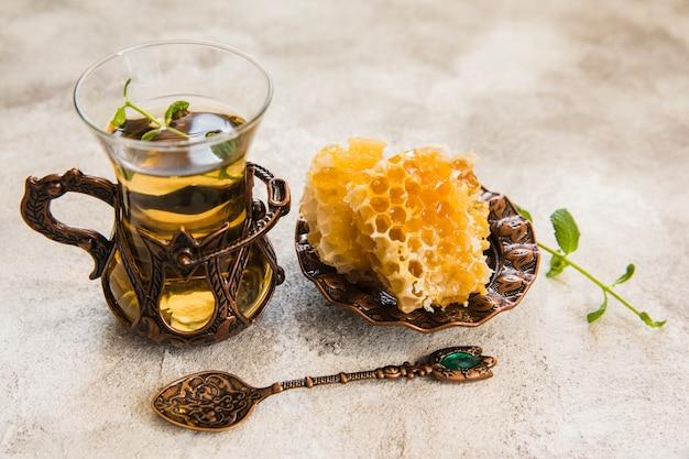 Copo de chá árabe com favo de mel na mesa