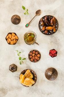 Copo de chá com frutas de datas e nozes na mesa