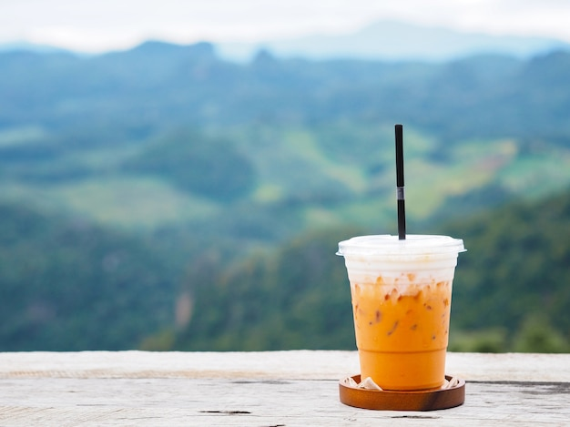 Copo de chá com leite gelado na mesa de madeira vintage sobre a floresta verde no fundo da montanha.