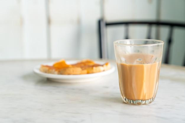 Copo de chá com leite tailandês quente na mesa Foto Premium