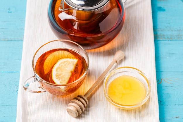 Copo de chá com limão, bule de vidro e mel.