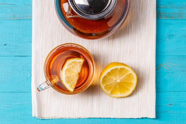Copo de chá com limão e bule de vidro.