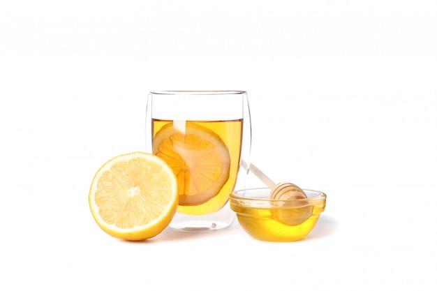 Copo de chá com limão, mel e dipper isolado no branco