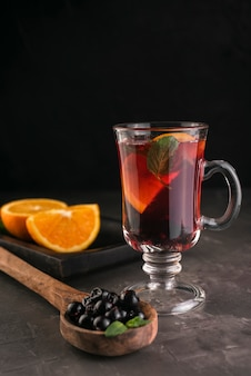 Copo de chá com mirtilos e fatias de laranja