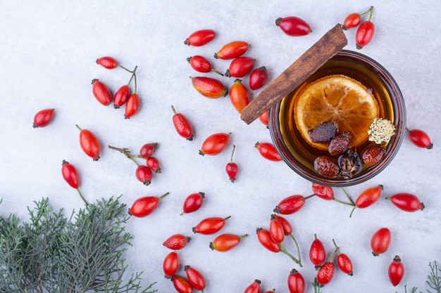 Copo de chá com rosa mosqueta, pau de canela e fatia de laranja.