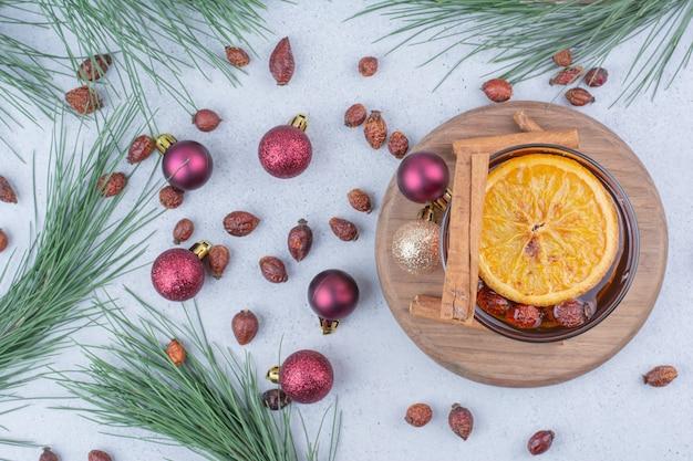 Copo de chá com rosehips e bolas de natal na superfície.