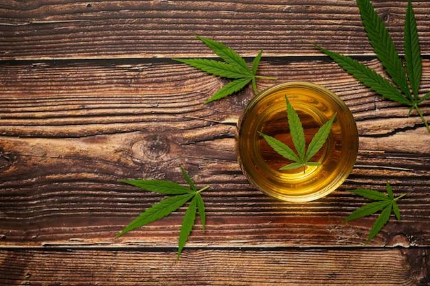 Copo de chá de cânhamo com folhas de cânhamo colocado no chão de madeira