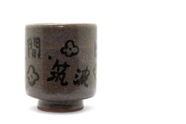Copo de chá de cerâmica estilo japonês no centro da imagem em fundo branco