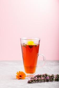 Copo de chá de ervas com calêndula e hissopo em um cinza e rosa