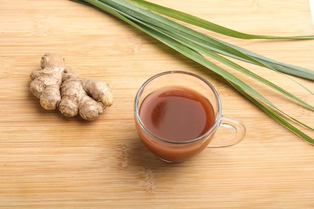 Copo de chá de gengibre quente com raiz de rizoma de gengibre cortada em superfície de madeira