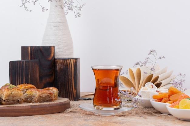 Copo de chá, doces e várias baklavas tradicionais na mesa de mármore.