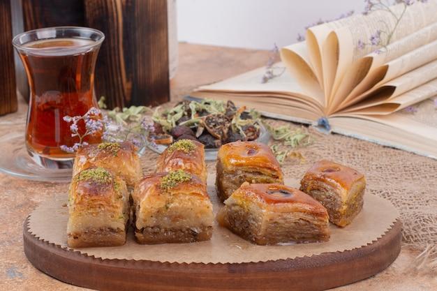 Copo de chá e baklava de pistache tradicional na mesa de mármore.