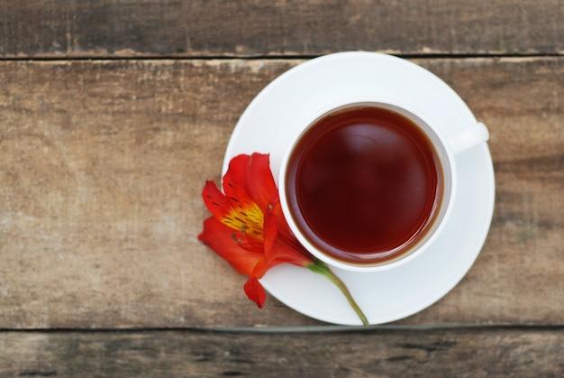 Copo de chá e flor alaranjada sobre de madeira rústico.