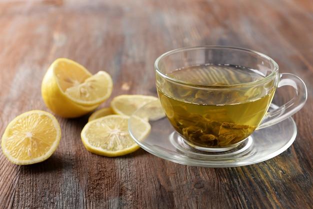 Copo de chá e limão fatiado em fundo de madeira