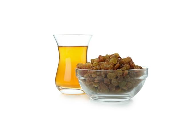 Copo de chá e tigela de passas isoladas na superfície branca